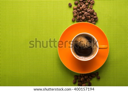 Orange cup of coffee on green background