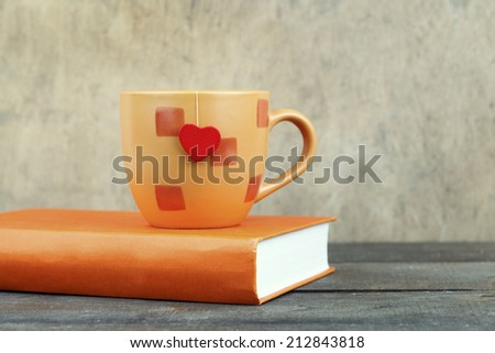 orange cup with red heart and book on grunge wooden table  - stock photo