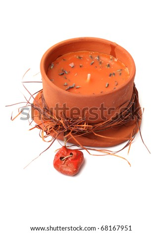Orange decorated candle in the clay ceramic tray