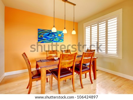 Orange Dining Room With Wood Table And Hardwood Floor.