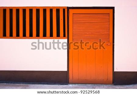 orange door closed on pink wall. - stock photo