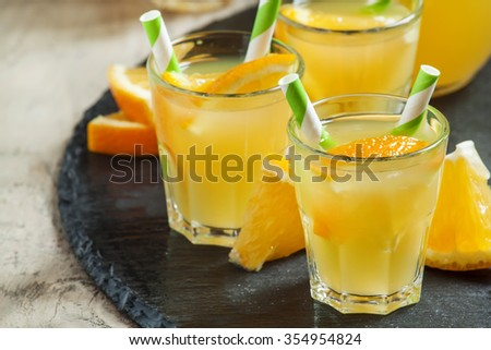 Orange drink in small glasses with striped straws and pitcher, selective focus