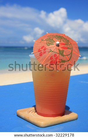 Orange drink umbrella against background distant sky. - stock photo