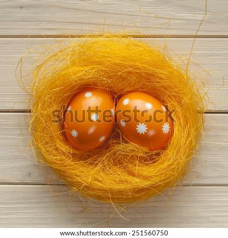 Orange Easter eggs in the nest - stock photo