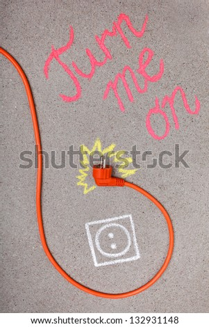 Orange electrical plug-in cable and chalk drawing of electrical outlet and electricity - stock photo