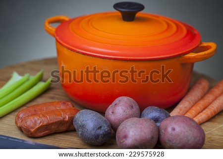 Orange enamel dutch oven on wood cutting board with potatoes, carrots, chorizo & celery arrayed - stock photo