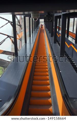 Orange escalator - stock photo