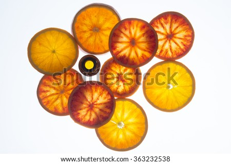 Orange essential oil bottle with orange slices (top view) - stock photo