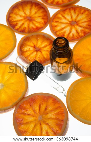 Orange essential oil in bottle with blood orange slices