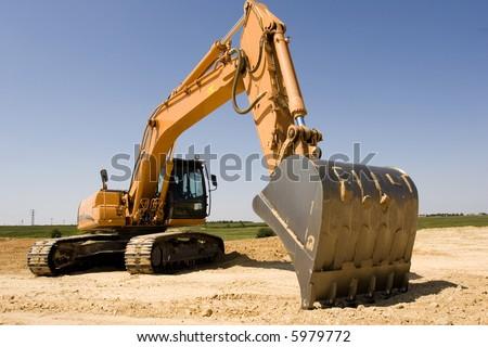 Orange excavator at construction site - stock photo