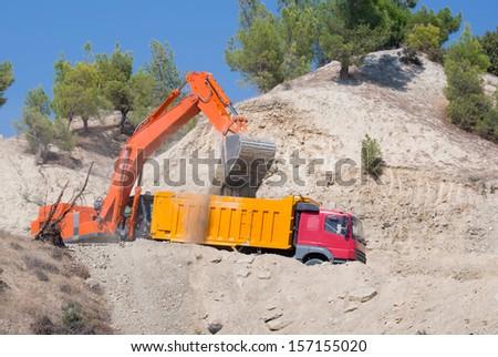 Orange excavator loading soil into a dumper truck on construction site  - stock photo