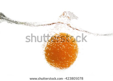 Orange falling into the water, and water splashes on a light background - stock photo