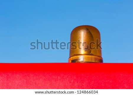 Orange flashing light installed on the roof of the red vehicle - stock photo