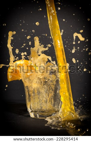 Orange flavoured soft drink with splashes in a glass with a dark background.