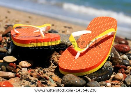 Orange flip-flops on the beach in Barcelona. - stock photo