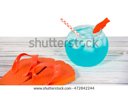 orange flip-flops on wood with drink in fish bowl