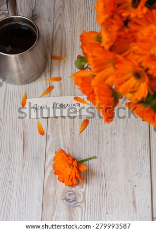 Orange flowers with coffee and good morning note