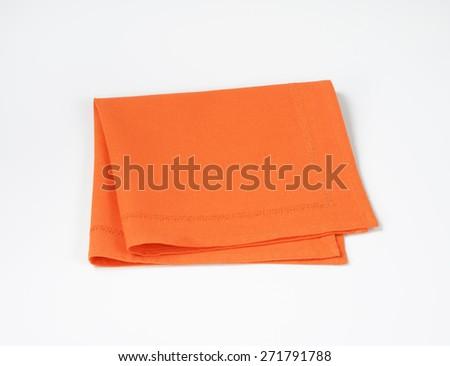 Orange folded napkin on white background - stock photo