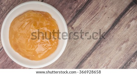 Orange fruit curd in white bowl over wooden background
