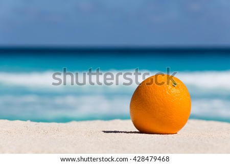 Orange fruit on sand against turquoise caribbean sea water. Tropical summer vacation concept