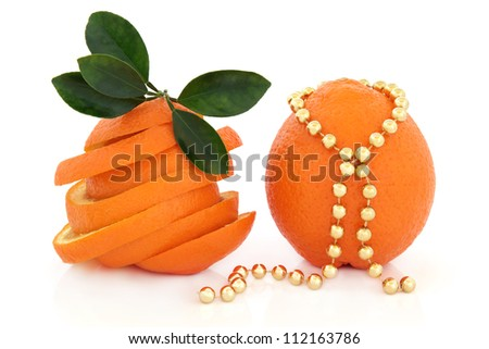 Orange fruit sliced with leaf sprigs and whole with strand of gold beads over white background.