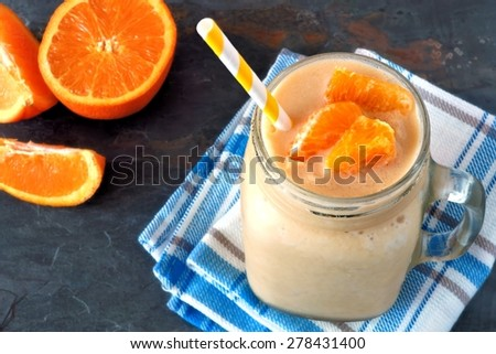 Orange fruit smoothie in a mason jar glass resting on checked cloth with fresh orange slices over a slate background - stock photo