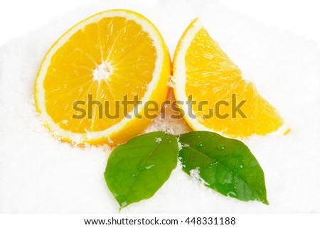 Orange fruit with citrus leaves on ice on white background - stock photo