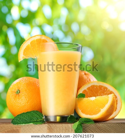 Orange fruits and glass of orange juice on wooden table.