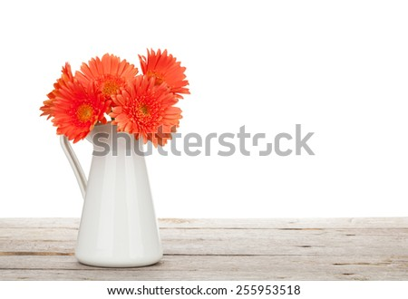 Orange gerbera flowers in pitcher on wooden table. Isolated on white background - stock photo