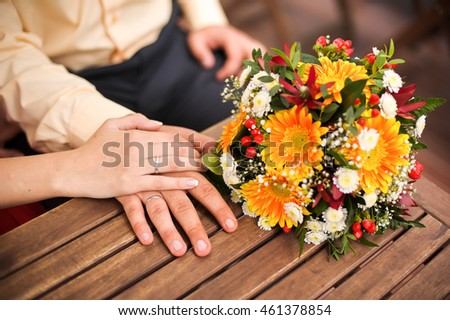 Orange gerberas bouquet on a wooden table, hands of a bride and groom