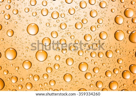 Orange glass surface covered with water drops texture.