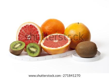 Orange, grapefruit, kiwi and tape measure in inches around, shot over white - stock photo