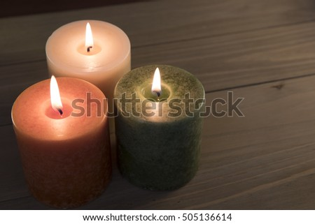 Orange, green and white candles burning on wooden table
