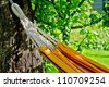 Orange hammock in green summer garden, close-up - stock photo