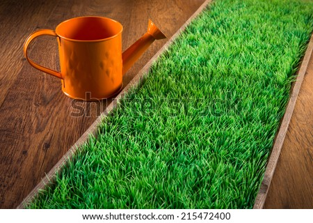 Orange hand sprinkler with green turf on hardwood floor. - stock photo