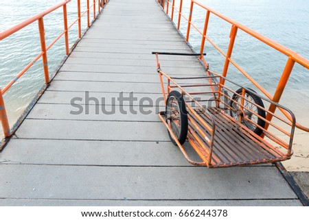 orange handcart parked on pier walkway with iron railings handcart used for carriage of goods