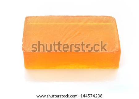 Orange handmade glycerin soap on white background. Hypoallergenic soap with marigold extract. Beauty care. - stock photo