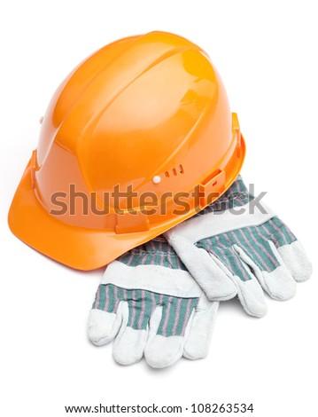 Orange hard hat on the gloves, isolated on white - stock photo