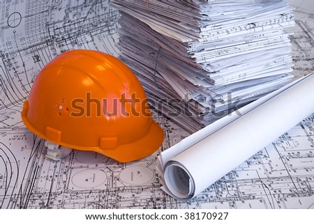 Orange helmet and heap of project drawings - stock photo