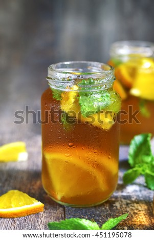 Orange iced tea in a glass jar on a rustic wooden background.