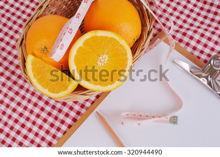 orange in basket ,centimeter and empty paper sheet chart on table cloth for lose weight concept - stock photo