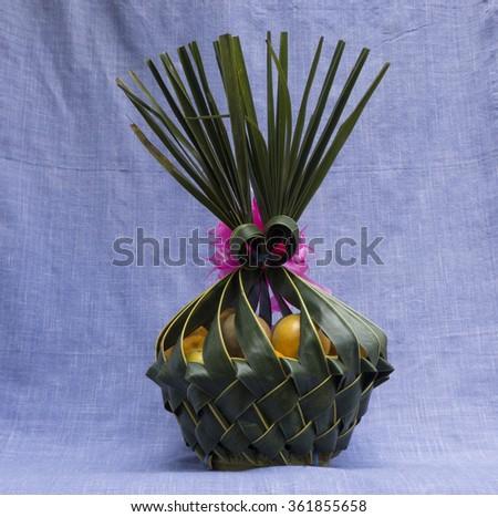 Orange in Coconut leaves basket on Purple cloth - stock photo