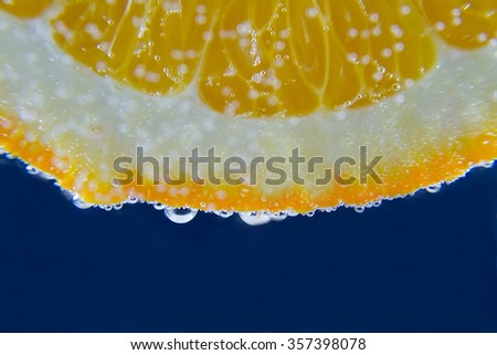 Orange in underwater with bubbles on dark blue background close-up macro - stock photo