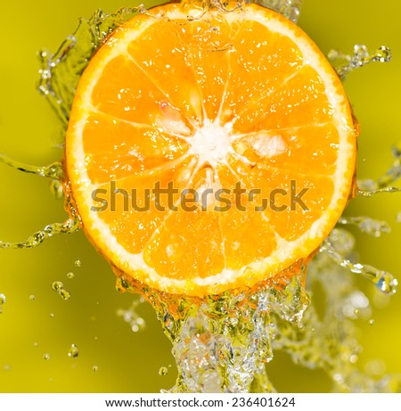 orange in water on a yellow background background - stock photo