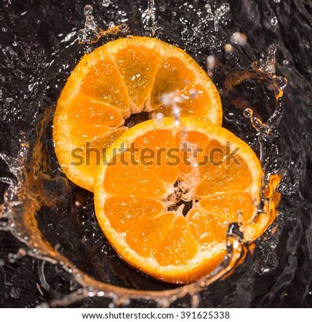 Orange in water splashes on a black background - stock photo
