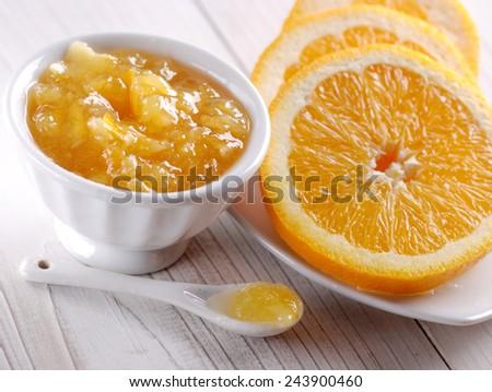 orange jam homemade into the jar white - stock photo
