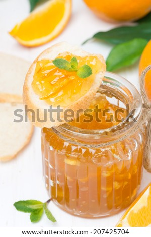 orange jam in a glass jar and fresh baguette, top view - stock photo