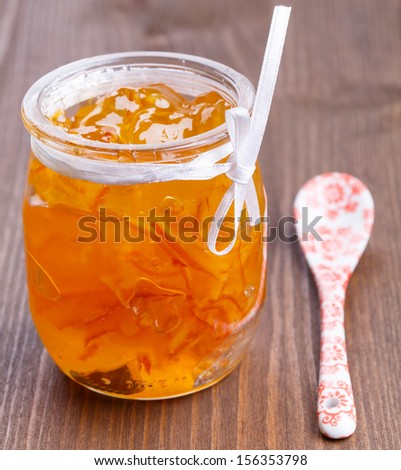 Orange jam in glass jar on wooden table - stock photo