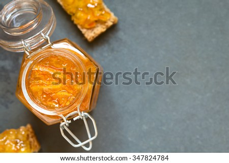 Orange jam in swing-top jar, bread slices with orange jam on the side, photographed overhead on slate with natural light (Selective Focus, Focus on the orange jam in the jar)  - stock photo