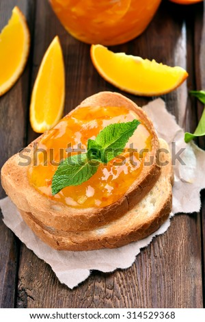 Orange jam on toast on wooden table, close up view - stock photo